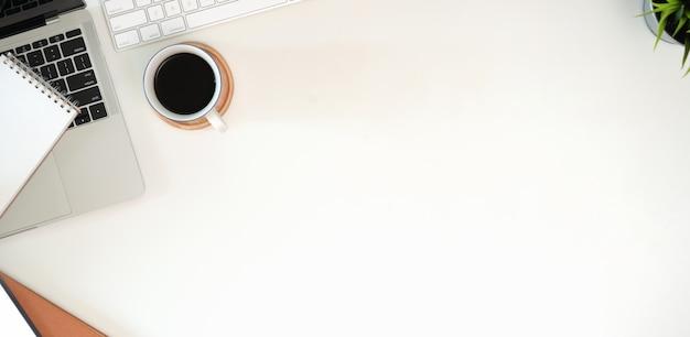 Local de trabalho minimalista elegante com teclado, laptop, material de escritório em estilo leigo plana Foto Premium