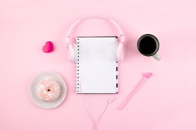 Local de trabalho mínimo com o bloco de notas em branco, fones de ouvido Foto Premium