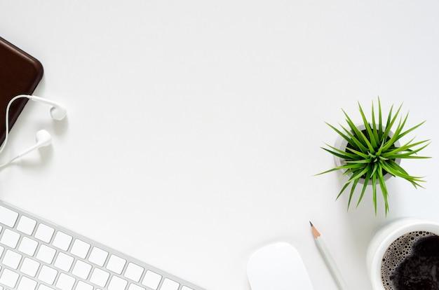 Local de trabalho moderno com teclado e rato sem fio, uma xícara de café, smartphone com fones de ouvido, lápis e planta de ar de tillandsia no fundo branco. vista superior, lay plana Foto Premium