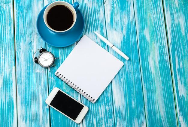 Local de trabalho moderno com uma xícara de café na mesa de madeira Foto Premium