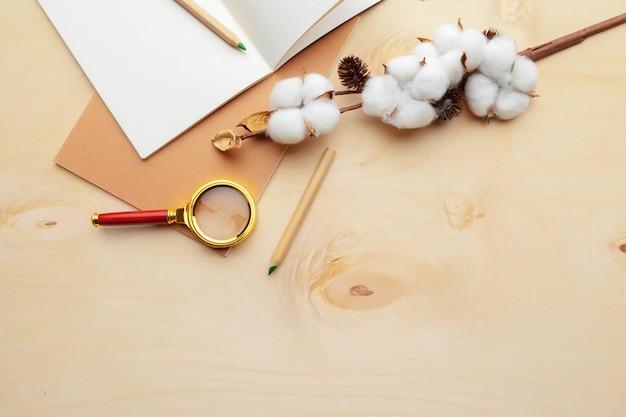 Local de trabalho moderno de cor bege na mesa de madeira com muitas coisas nele. vista do topo Foto Premium