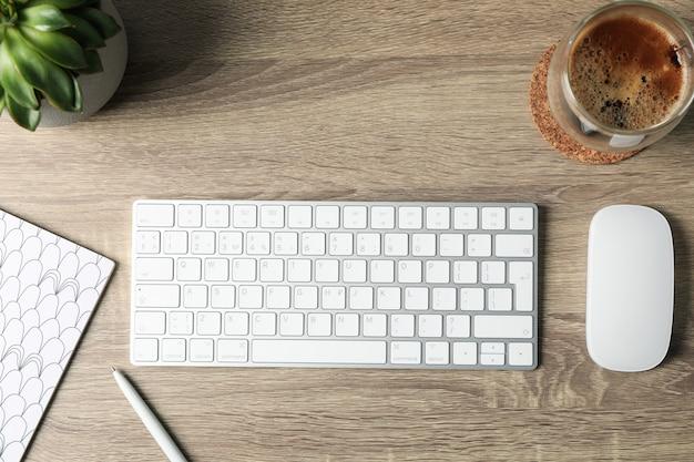 Local de trabalho. teclado, mouse, planta, xícara de café e notebook em madeira, vista superior Foto Premium