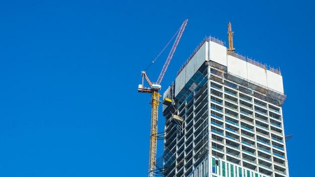 Local do guindaste e da construção civil contra o céu azul com o quadro de avisos branco vazio para a propaganda na parte superior da arquitetura da torre. Foto Premium