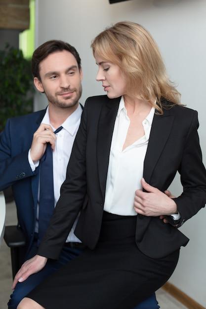 Loira adorável flerta com o chefe no escritório, sentado no colo Foto Premium