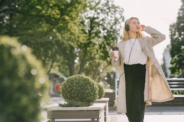 Loira caminha na cidade de verão com uma xícara de café Foto gratuita