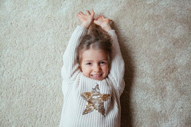 Loira criança bonitinha sorrindo no chão Foto Premium