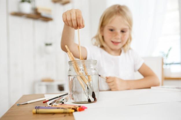 Loira criativa e alegre com sardas, mergulhando o pincel na água. criança do sexo feminino loira pintando com um pincel. atividades de arte para crianças. Foto gratuita