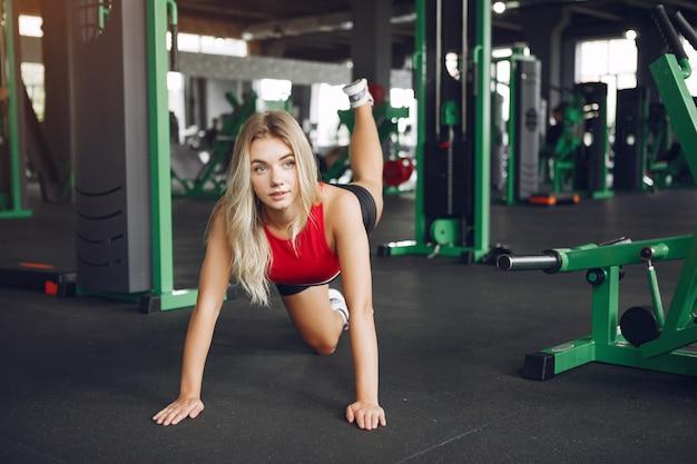 Loira de esportes em um sportswear descansar em uma academia Foto gratuita