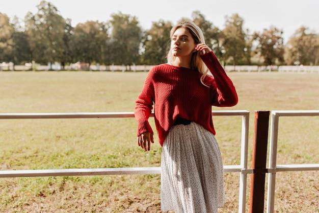 Loira elegante, aproveitando o sol brilhante na zona rural de outono. linda garota posando com alegria de blusa vermelha e vestido branco ao ar livre. Foto gratuita