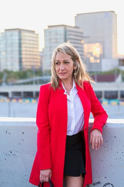 Loira empresária vestindo jaqueta vermelha e camisa preta em pé na cidade enquanto olhando para longe Foto Premium