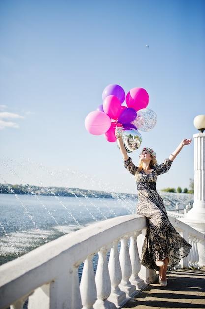 Loira garota com balões na festa da galinha contra o lago. Foto Premium
