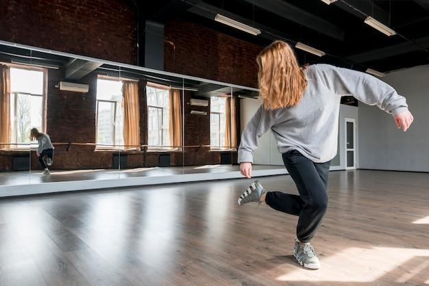 Loira jovem dançando contra o espelho no estúdio de dança Foto gratuita