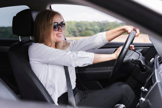 Loira jovem dirigindo um carro Foto gratuita