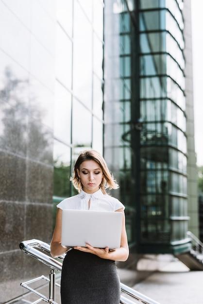 Loira jovem empresária em pé na frente do prédio usando o laptop Foto gratuita
