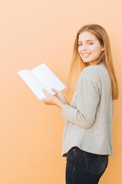 Loira jovem segurando o livro na mão, olhando para a câmera contra o fundo de pêssego Foto gratuita