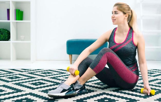 Loira jovem sentada no tapete em casa segurando halteres amarelos na mão Foto gratuita