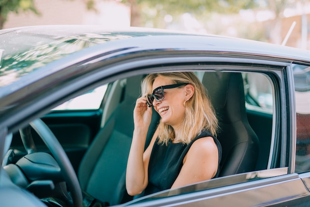 Loira jovem sentado no carro rindo Foto gratuita