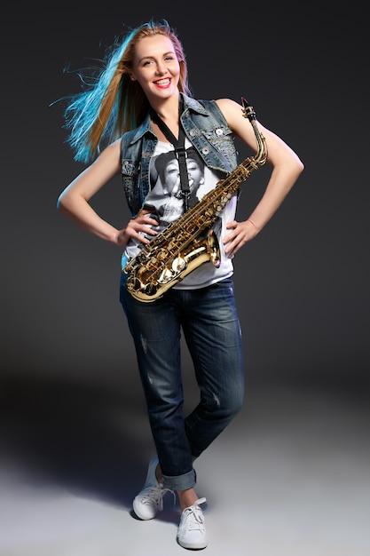 Loira linda como mulher saxofonista Foto gratuita