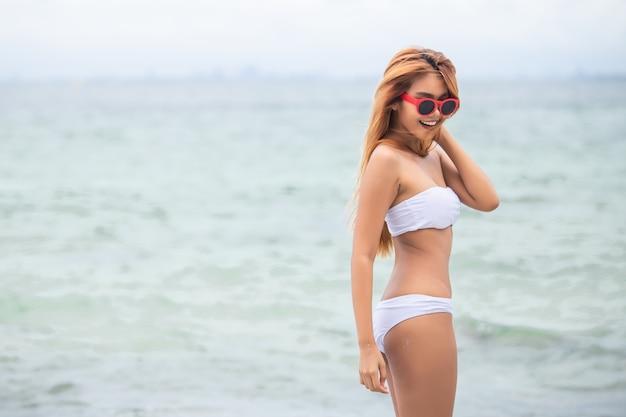 Loira linda garota em biquíni branco fica na praia. Foto Premium