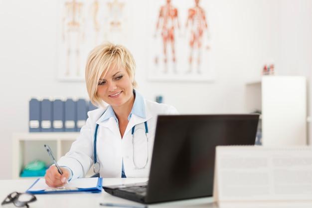 Loira linda médica trabalhando em seu escritório Foto gratuita