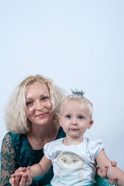 Loira mãe e filha em estúdio na superfície branca Foto Premium
