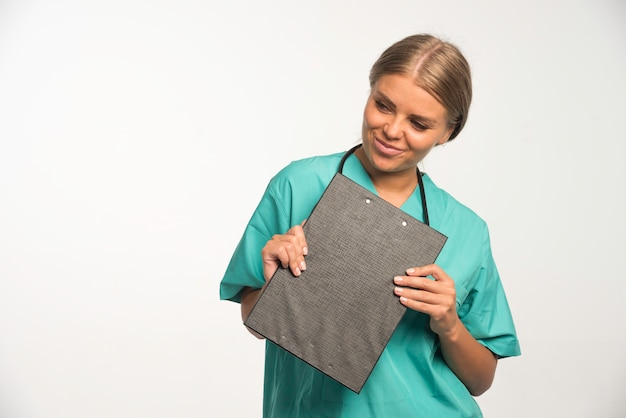 Loira médica de uniforme azul, segurando um livro de recibos e sorrindo. Foto gratuita