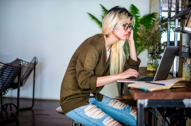 Loira mulher asiática trabalhando em um laptop Foto gratuita