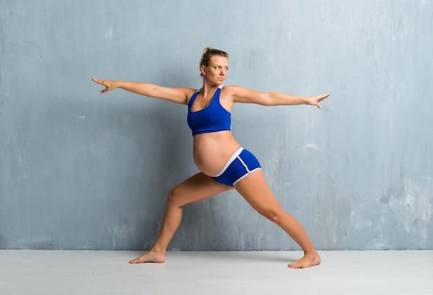Loira mulher grávida fazendo yoga Foto Premium