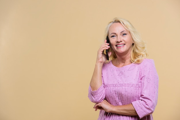 Loira mulher sênior falando ao telefone com espaço de cópia Foto gratuita