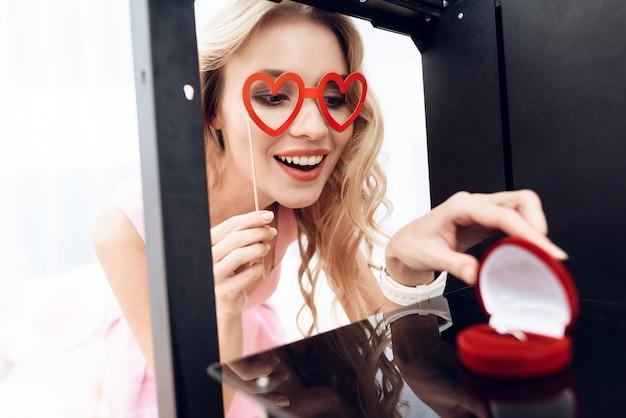 Loira olha para o anel de casamento em uma impressora 3d. Foto Premium