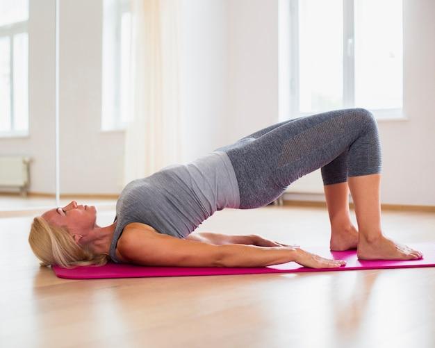 Loira sênior mulher exercitando ioga Foto gratuita
