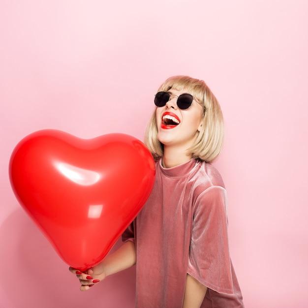Loira sexy abraçando em forma de um coração uma bola vermelha e sorrindo. Foto Premium