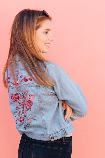 Loira sorridente jovem mulher com os braços cruzados contra o fundo rosa Foto gratuita