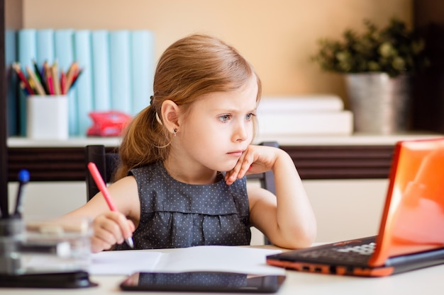 Loirinha fazendo lição de casa em casa na mesa. a criança é educada em casa. uma garota de cabelos claros executa uma tarefa on-line usando um laptop e tablet. Foto Premium
