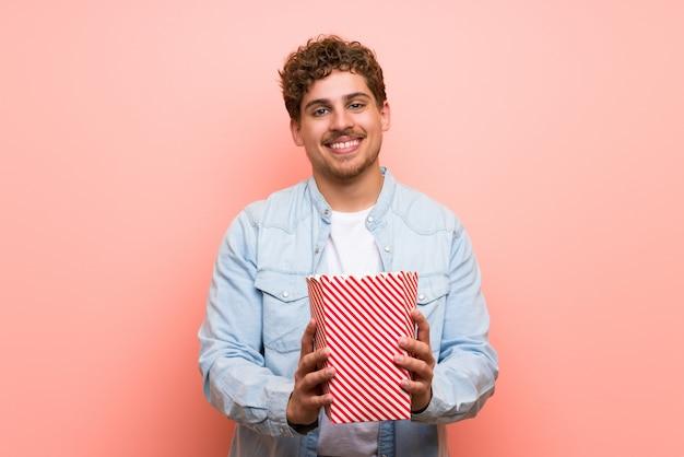Loiro, homem, sobre, parede cor-de-rosa, comer, pipocas Foto Premium