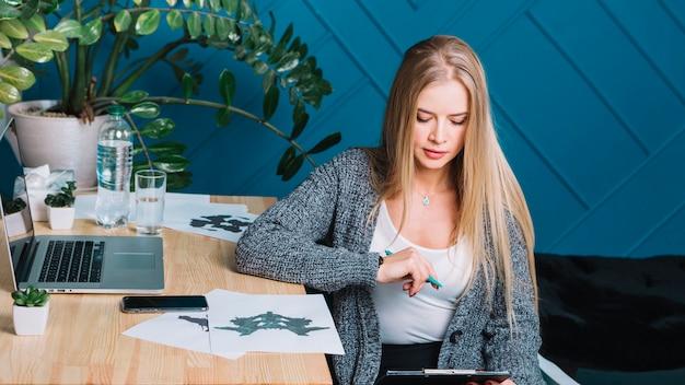 Loiro, jovem, femininas, psicólogo, analisar, a, rorschach, inkblot, teste, em, escritório Foto gratuita