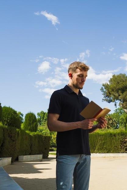 Loiro, menino, leitura, parque Foto gratuita