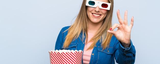 Loiro, mulher, comer, pipocas, mostrando, um, tá bom sinal, com, dedos Foto Premium