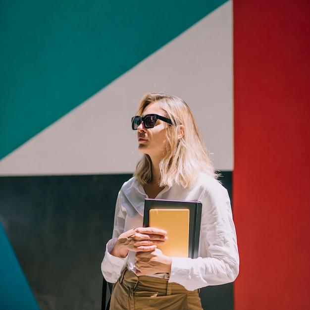 Loiro, mulher jovem, desgastar, pretas, óculos, segurando, livro, em pé mão, frente, e, colorido, e = wall Foto gratuita