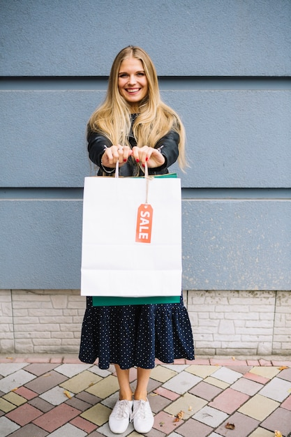 Loiro, mulher jovem, ficar, contra, parede, mostrando, bolsas para compras, com, venda, tag Foto gratuita