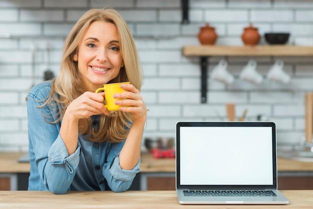 Loiro, mulher jovem, segurando, xícara café, com, laptop, ligado, tabela madeira Foto gratuita