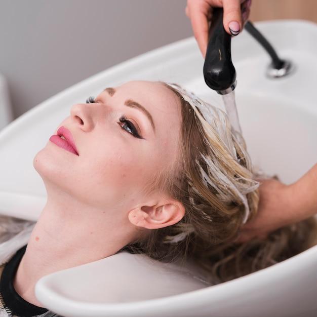 Loiro, mulher, obtendo, dela, cabelo, lavado Foto gratuita