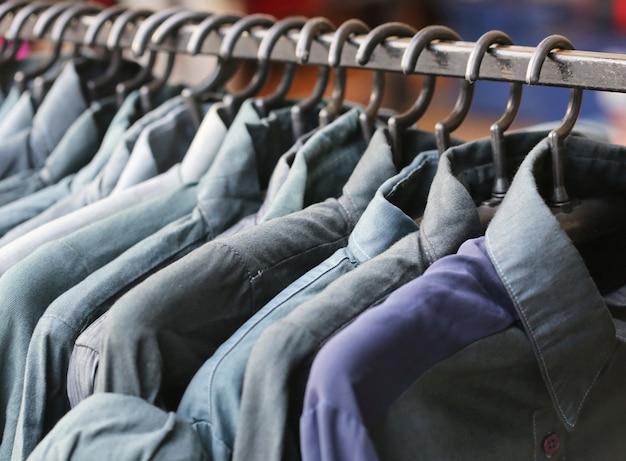 Loja de camisa azul, através de novas roupas durante as compras Foto Premium
