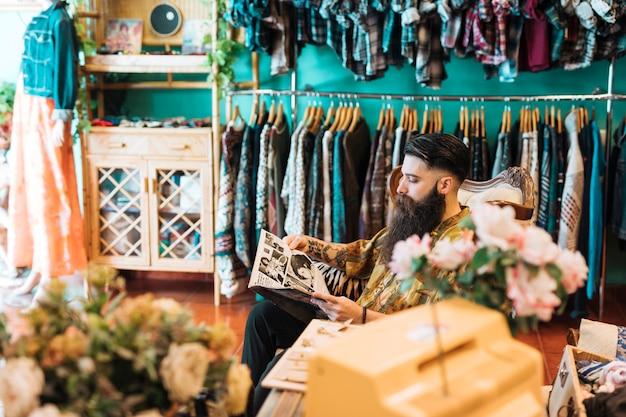 Loja masculino proprietário sentado na cadeira em sua loja de roupas Foto gratuita
