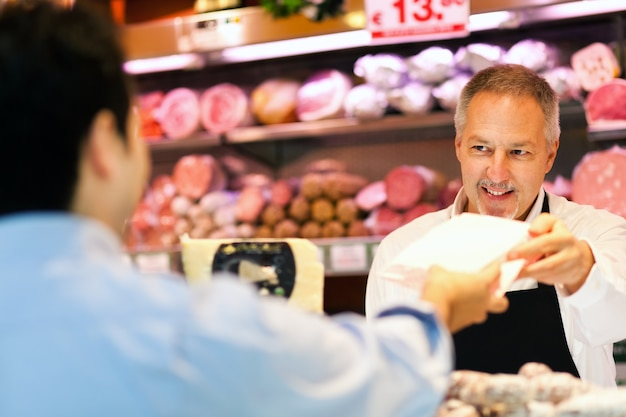 Lojista, servindo, um, cliente, em, um, mercearia Foto Premium