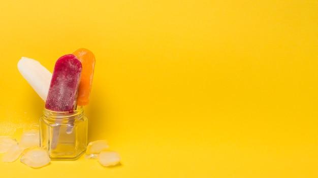 Lolly de gelo colorido em jarra perto de gelo Foto gratuita