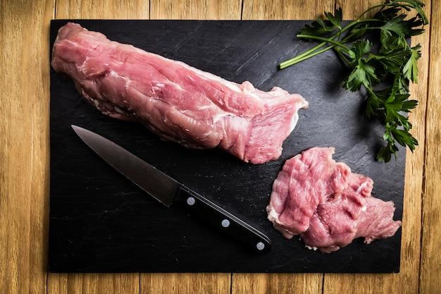Lombo de porco picado ao lado de uma faca e alguns ramos de salsa Foto Premium