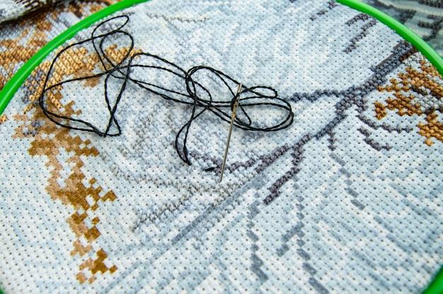 Lona de tela plana com um belo padrão de linhas de costura brilhantes e uma agulha para close-up de bordados Foto Premium