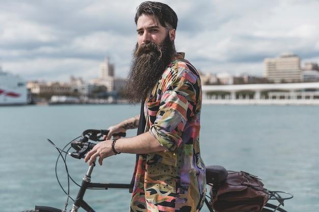 Long barbudo jovem de pé com bicicleta perto da costa Foto gratuita