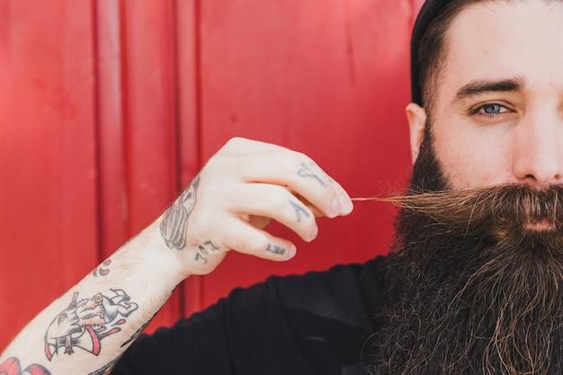 Long barbudo jovem puxando o bigode contra a parede de madeira Foto gratuita